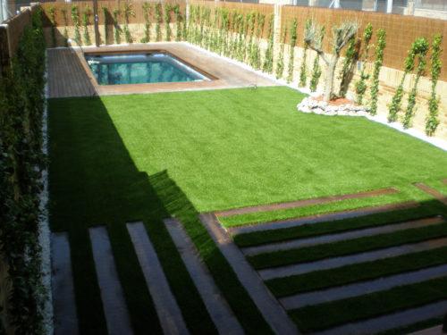 Jardín particular de césped artificial con entarimado en Madrid.