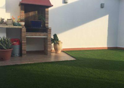 Césped artificial junto a barbacoa en un jardín de Alicante