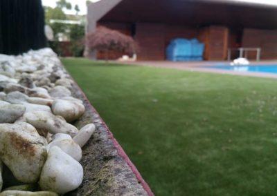 Detalle de instalación de césped artificial junto a piscina en Asturias