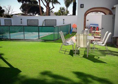Césped artificial junto a piscina en jardín de Cádiz