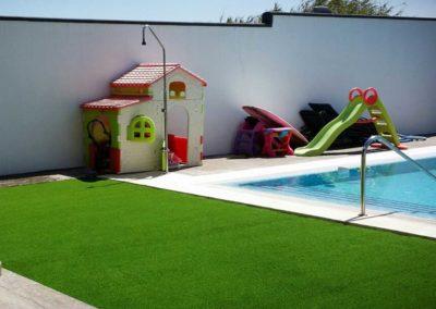 Detalle de zona infantil y piscina en jardín de Cádiz con césped artificial