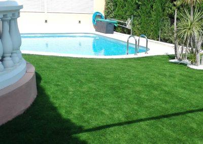 Jardín con instalación de césped artificial junto a piscina en Castellón