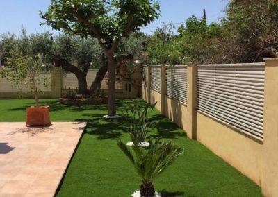 Césped artificial junto a vegetación natural en jardín de Castellón