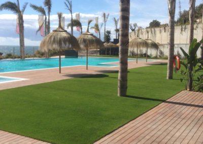 Césped artificial junto a tarima y piscina en Málaga