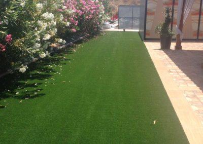 Entrada a jardín con césped artificial en Murcia