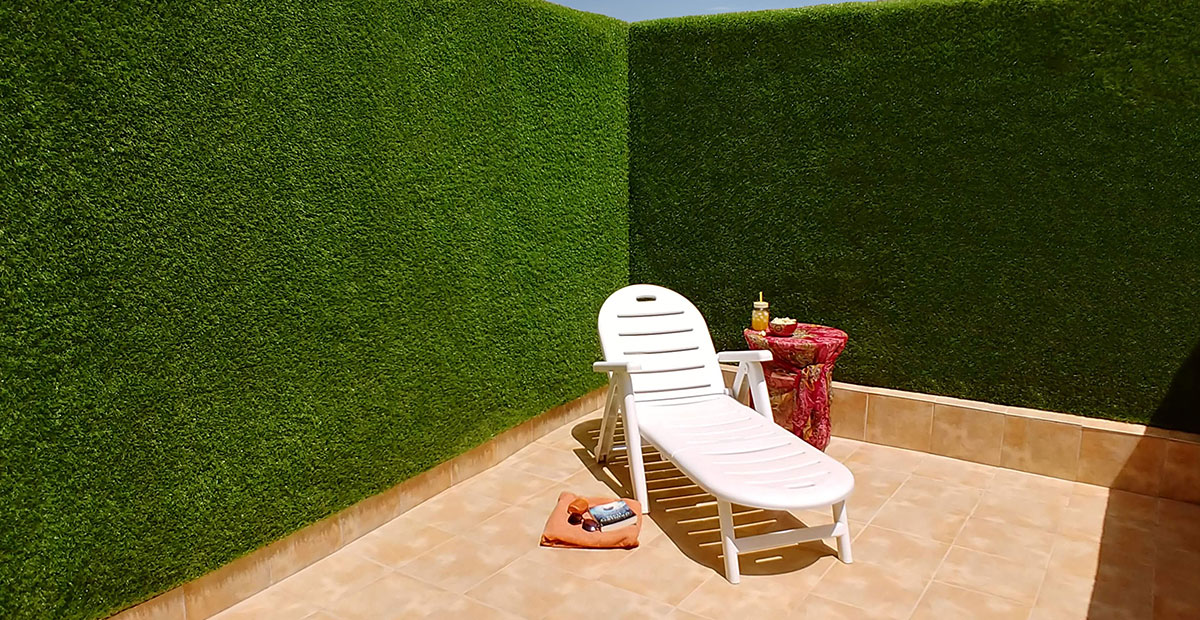 Terraza con jardín vertical de césped artificial